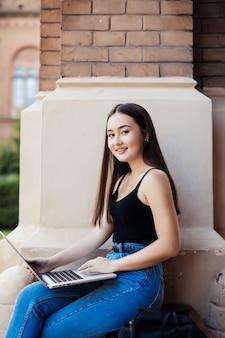 Zamyka up żeński studenta collegu obsiadanie w gazonie używać jej laptop na słonecznym dniu.