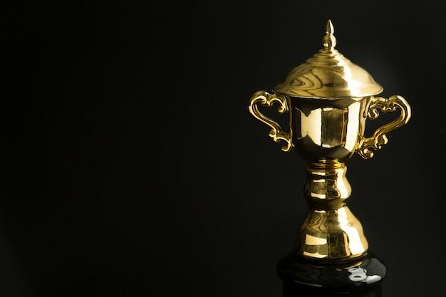 Zamyka up złoty trofeum nad czarnym tłem. zwycięskie nagrody z miejsca kopiowania tekstu i projektowania.