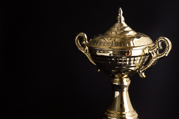 Zamyka up złoty trofeum nad czarnym tłem. zwycięskie nagrody