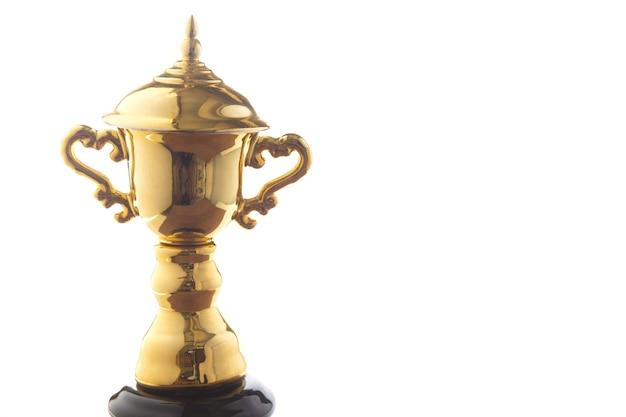 Zamyka up złoty trofeum odizolowywający na białym tle. zwycięskie nagrody