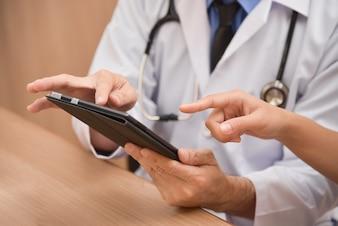 Zamyka w górę Azjatyckiej samiec lekarki wręcza używać cyfrowego pastylka komputer.