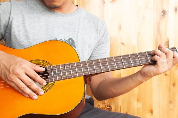 Zamyka w górę azjatykciego mężczyzna bawić się gitarę