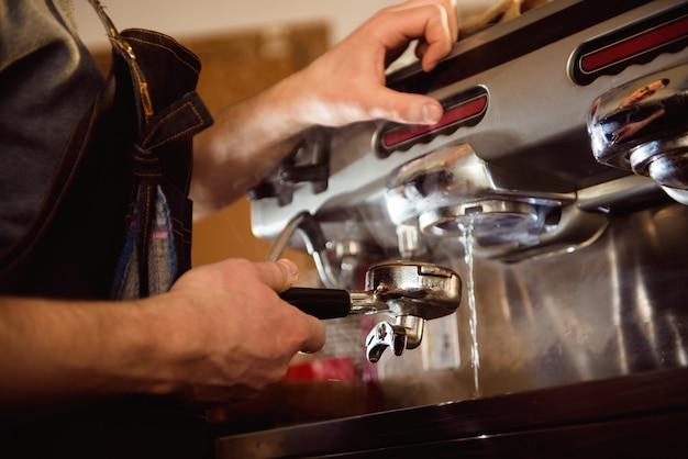 Zamyka w górę barista ręki robi filiżance kawy