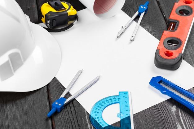 Zamyka w górę białego hardhat i rozmaitości remontowi narzędzia z copyspace w środku nad drewnianym