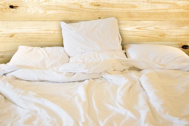 Zamyka w górę białych pościeli prześcieradła i poduszki, upaćkany łóżkowy pojęcie