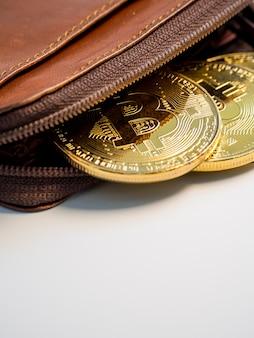 Zamyka w górę bitcoin złotych monet z portflem na białym tle. koncepcja wirtualnej kryptowaluty.