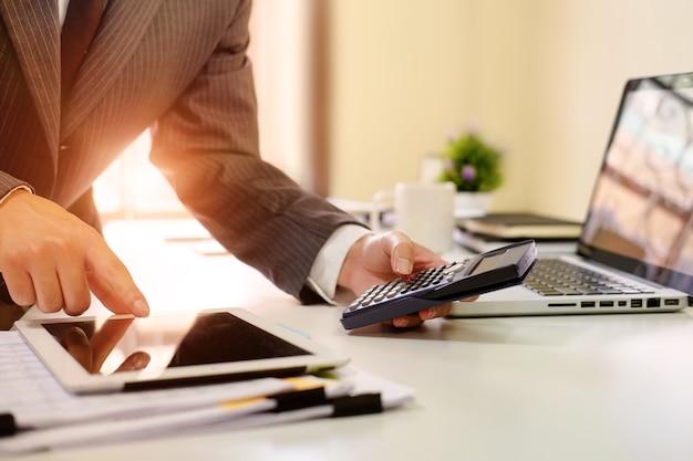 Zamyka w górę biznesmena kalkuluje pieniężnych dane w pastylka komputerze i kalkulatorze.