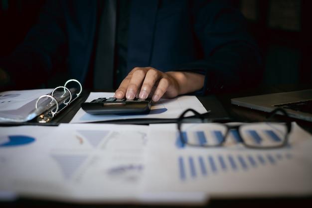 Zamyka w górę biznesmena używa kalkulatora i laptop dla robimy matematyka finansowi na drewnianym biurku