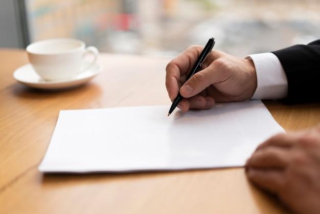 Zamyka w górę biznesowego mężczyzna bierze notatki