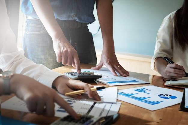 Zamyka w górę biznesowej kobiety i partnera używa kalkulatora i laptop dla calaulating finanse