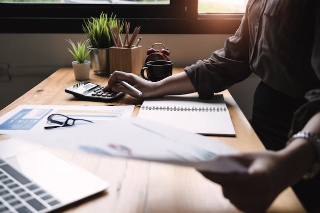 Zamyka w górę biznesowej kobiety używa kalkulatora dla robi matematyka finansowi na drewnianym biurku w biurze