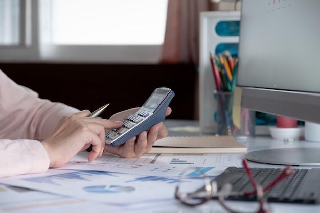 Zamyka w górę biznesowej kobiety używa kalkulatora i laptopu dla robi matematyka finansowi na drewnianym biurku w biurze