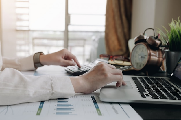 Zamyka w górę biznesowej kobiety używa kalkulatora i laptopu dla robi matematyka finansowi na drewnianym biurku