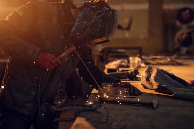 Zamyka w górę bocznego widoku skupiający się profesjonalny spawacz z maską ochronną pracuje przy stołem w pogodnym tkaninie warsztacie