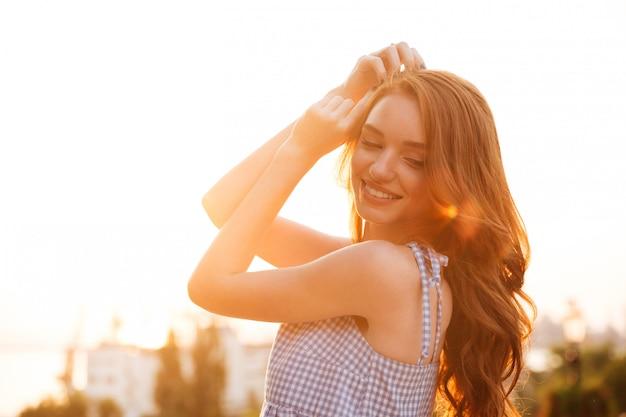 Zamyka w górę bocznego widoku uśmiechnięta ładna imbirowa kobieta