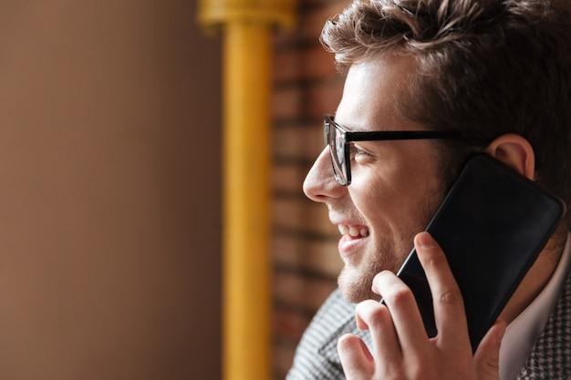Zamyka w górę bocznego widoku uśmiechnięty biznesmen w eyeglasses