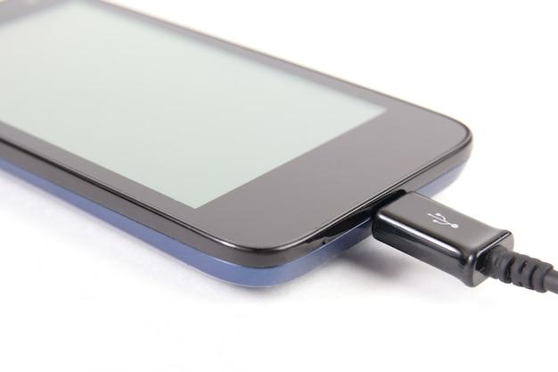 Zamyka w górę czarnego smartphone i usb kabla odizolowywającego na białym tle