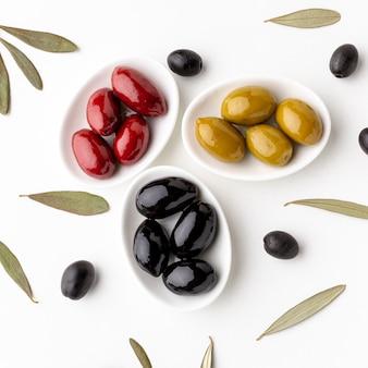 Zamyka w górę czerwonych czarnych żółtych oliwek na talerzach