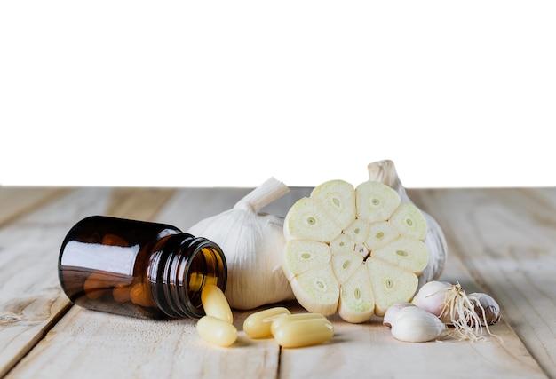 Zamyka w górę czosnku i oleju kapsuły gel dodatku na drewnianym białym tle