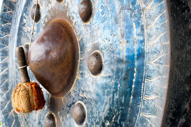 Zamyka w górę dobniaka obwieszenia na zamazanym dużym gongu przy świątynnym, dużym gongiem w świątyni, tajlandia