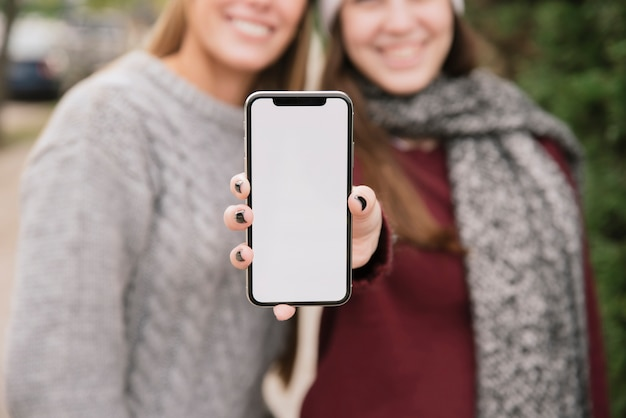 Zamyka w górę dwa uśmiechniętych kobiet trzyma telefon w rękach
