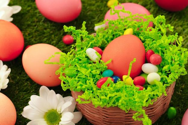 Zamyka w górę fotografii barwioni wielkanocni jajka i cukierki na trawie