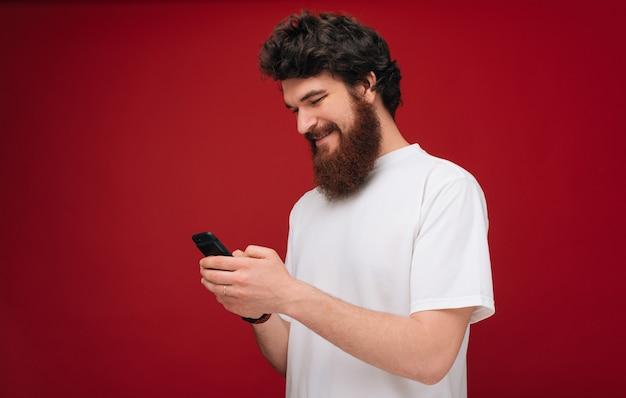 Zamyka w górę fotografii brodaty facet używa wiszącą ozdobę, ubierającą w białym tshirt nad czerwieni ścianą