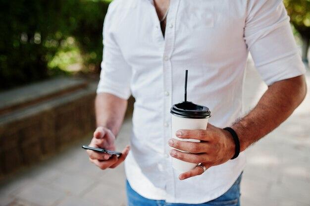 Zamyka w górę fotografii facet z filiżanką kawy i telefonem komórkowym przy rękami