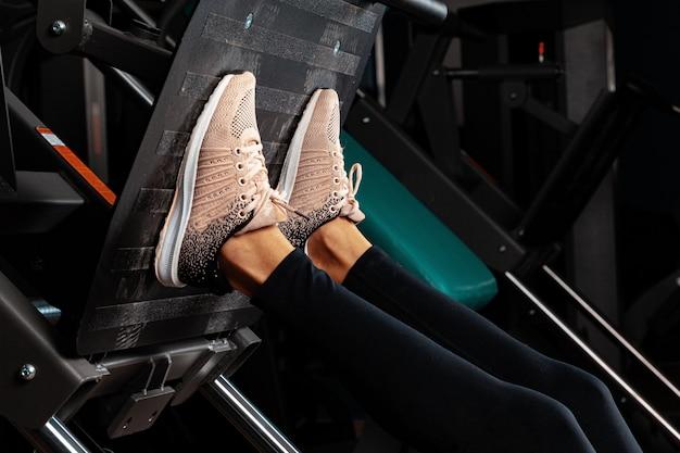 Zamyka w górę fotografii kobieta robi nogi prasie w ciemnym gym