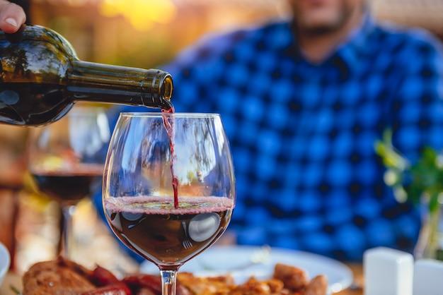 Zamyka w górę fotografii mężczyzna nalewa czerwone wino