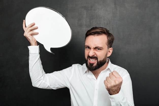 Zamyka w górę fotografii pomyślny mężczyzna trzyma pustego mowa bąbel zachęcający być motywowanym i ambitny nad ciemnoszarym ściany kopii przestrzenią