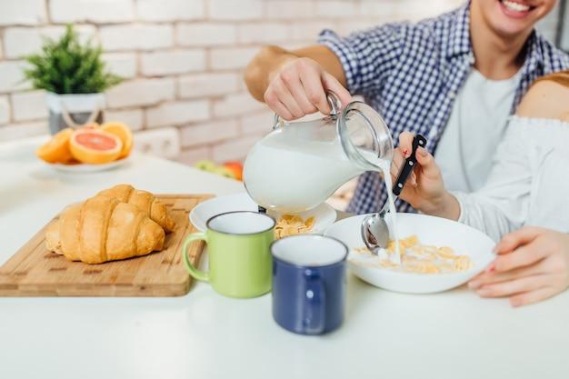 Zamyka w górę fotografii ranku biurko z zbożem, mlekiem i rogalikiem, zdrowy jedzenie. mężczyzna trzyma mleko