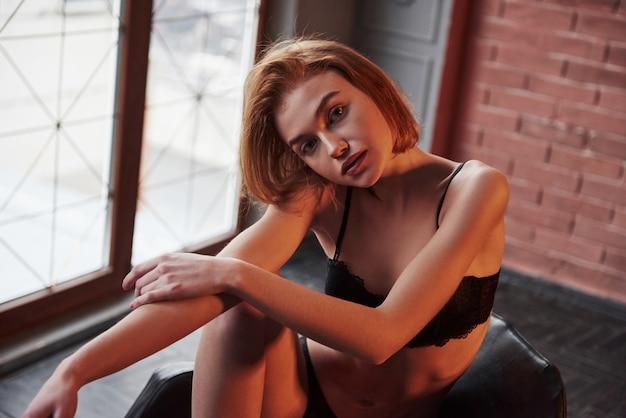 Zamyka w górę fotografii wspaniała młoda dziewczyna w bielizny obsiadaniu na krześle