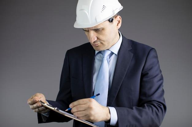 Zamyka w górę inżyniera budowlanego w ciężkim kapeluszu robi notatkom w schowku
