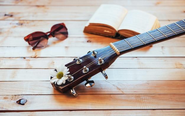 Zamyka w górę klasycznej gitary głowy z szkłami i książką