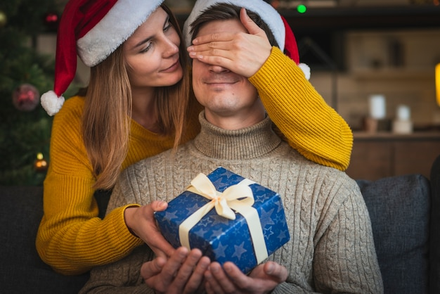 Zamyka w górę kobieta zaskakującego mężczyzna z prezentem