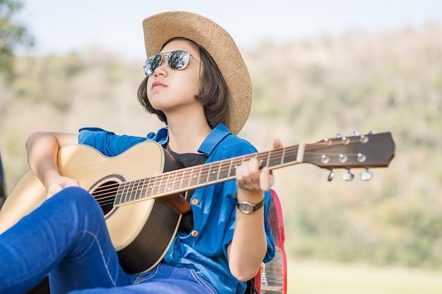 Zamyka w górę kobiety odzieży kapeluszu i bawić się gitarę