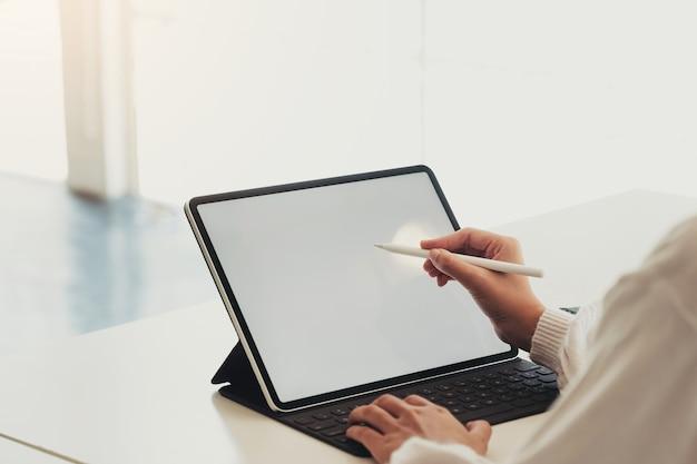 Zamyka w górę kobiety wskazuje z piórem przy pustym laptopu ekranu obsiadaniem w kawiarni na drewnianym stole