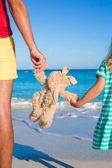 Zamyka w górę królik zabawki w rękach córka i tata na dennym tle