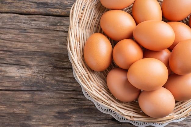 Zamyka w górę kurczaków jajek na drewnianym stole