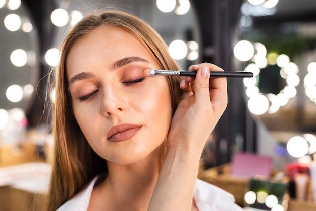 Zamyka w górę makijażu artysty stosuje eyeshadow na kobiecie z muśnięciem
