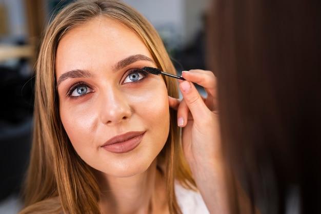 Zamyka w górę makijażu artysty stosuje tusz do rzęs na kobiecie