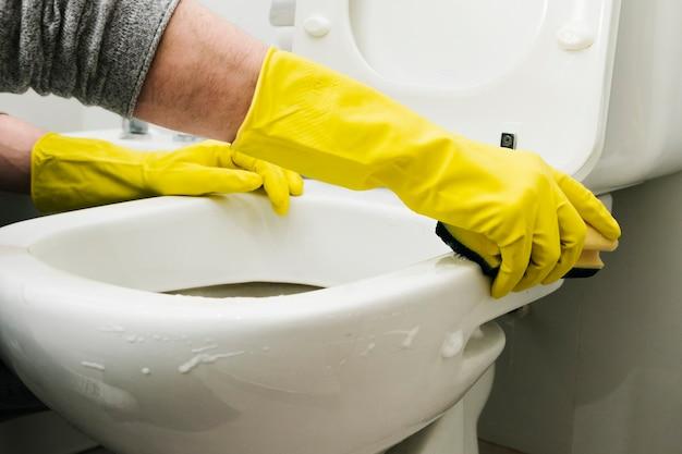 Zamyka w górę mężczyzna cleaning toalety z gąbką