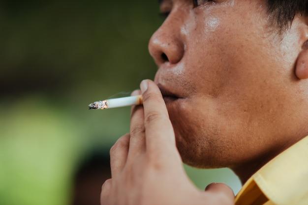 Zamyka w górę mężczyzna dymi papieros