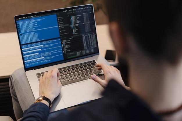 Zamyka w górę mężczyzna pisze kodzie na laptopie