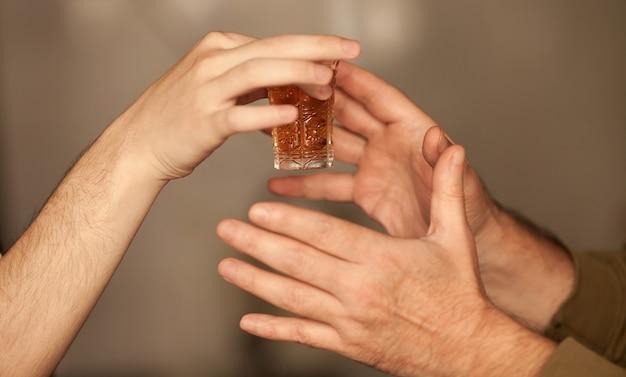 Zamyka w górę mężczyzna ręki bierze szkło z alkoholem
