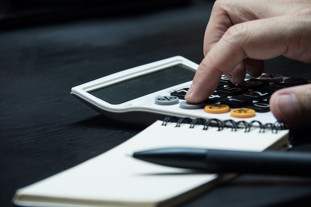 Zamyka w górę mężczyzna ręki używać kalkulatora na drewnianym biurka tle.
