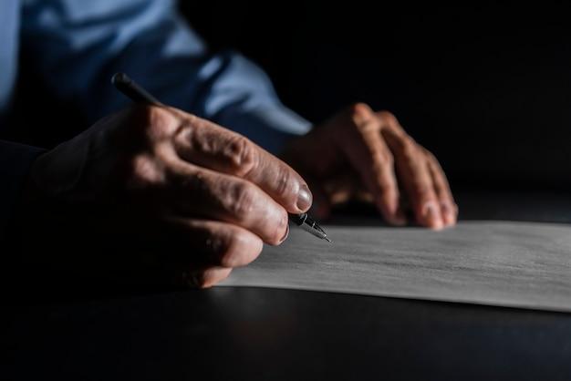 Zamyka w górę mężczyzna writing na papierze