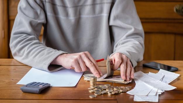 Zamyka w górę mężczyzna z kalkulatora liczeniem, robi notatkom w domu, ręka pisze w notatniku. ułożone monety u deeska. koncepcja finansów oszczędnościowych.