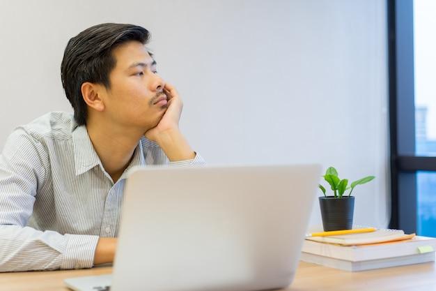 Zamyka w górę młodego azjatykciego mężczyzna uczucia znudzonego i śpiącego przy biurkiem, stylu życia pojęcie